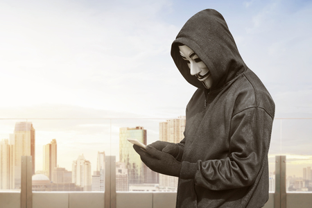Hacker with mask using smartphone to steal data on the office