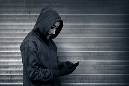 Hooded man with vendetta mask using mobile phone against roller shutter background Editorial