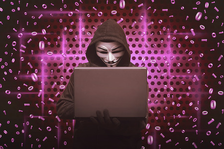 Hooded man wearing mask typing on laptop with binary code in background Editorial