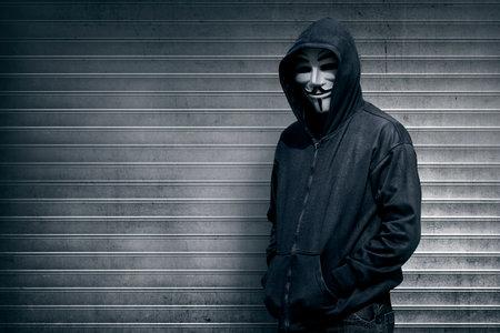 hombre anónimo en el fondo de la puerta del obturador gris Editorial