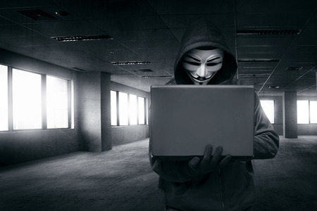 Hacker with mask using laptop on the empty dark room