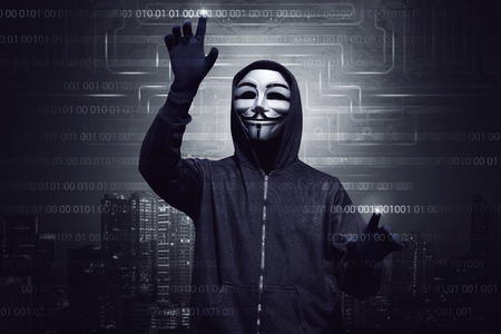 Hooded hacker with mask using virtual screen to hacking system security against digital modern city background