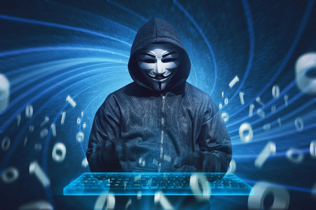 Hooded hacker with mask typing on virtual keyboard against digital background Editorial