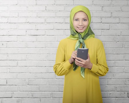 Asian muslim woman standing while using smartphone over white wall background