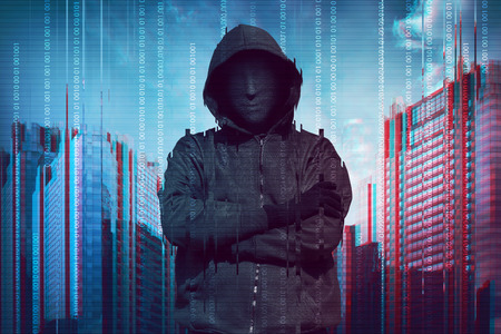 Hooded man wearing guy fawkes mask with binary data system security
