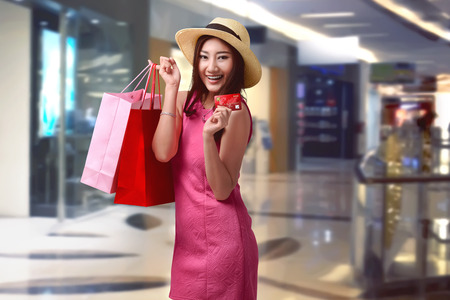 lifestyle shopping: Young asian woman holding shopping bags and show her credit card inside a mall