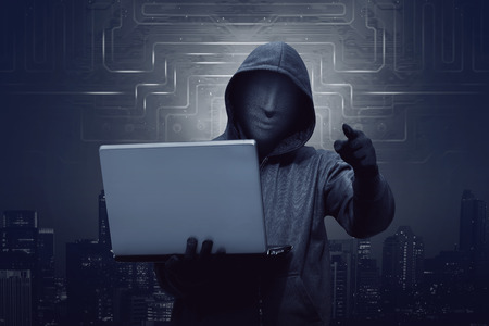 appoint: Hacker man with mask holding laptop while appoint against virtual background
