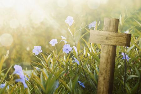 Cruz de madera y flor morada con luz del sol en el campo Foto de archivo - 71754823