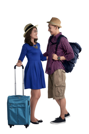 Smiling asian couple tourist with suitcase looking each other isolated over white background Stock Photo