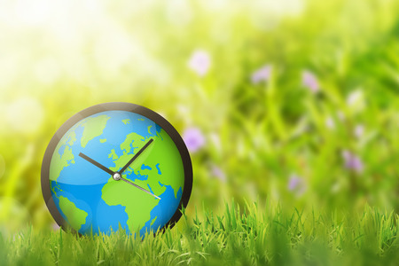 Clock of earth in the field. Earth Hour Concept.