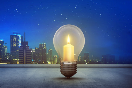 Burning candle inside light bulb on floor with modern city background