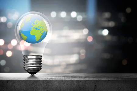 Portrait of earth inside light bulb over blurred light city background Standard-Bild