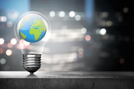 Portrait of earth inside light bulb over blurred light city background Stockfoto