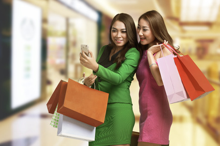 Two young asian woman with shopping bag looking at mobile phone after shopping Stock Photo