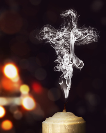 jesus praying: Candle smoke in the shape of a cross over blurred light background