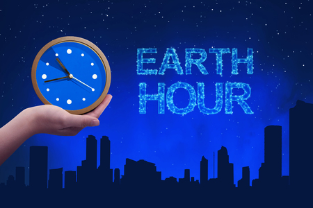 People hand holding a clock with earth hour greeting against a background night scene