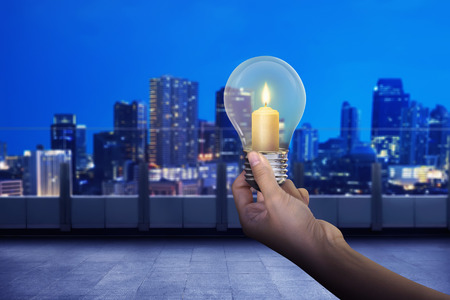 Hand die gloeilamp met glanzende kaars binnen het op moderne stadsachtergrond houdt Stockfoto