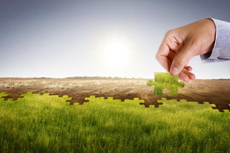 Geschäftsmann Hand zusammenbauen Puzzle, um neue Welt mit frischen Umwelt zu bauen. Klimawandelkonzept