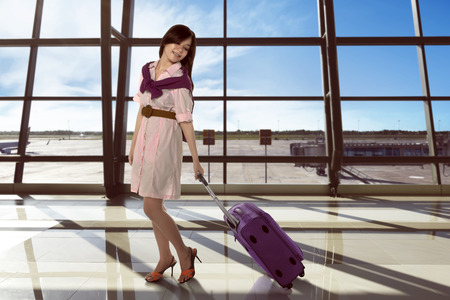 Young asian woman walking at departure lounge with suitcase against window glasses background photo