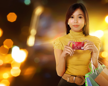 Beautiful asian woman with shopping bags and credit card in the hands over blurred background photo
