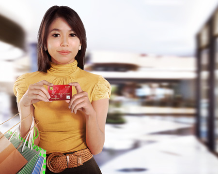 Pretty asian woman with shopping bag showing credit card in the mall photo