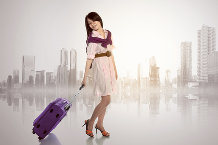Happy asian woman with scarf holding suitcase against cityscape background photo