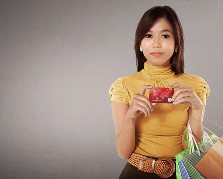 Happy asian woman with many shopping bags and credit card in her hand against grey background photo