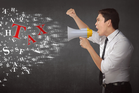 businessman using a megaphone: Young asian businessman using megaphone shouting notice TAX against wall background