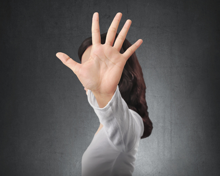 Portrait of asian woman showing stop with hand gesture with black wall background Imagens