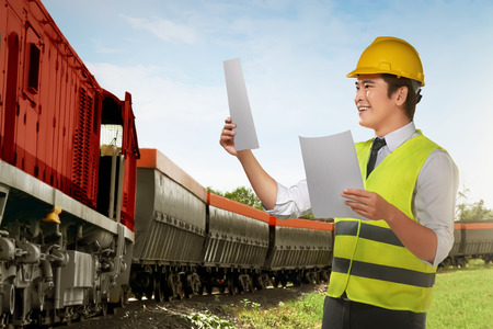 Young asian worker checking on train machine in the tracks Stock Photo