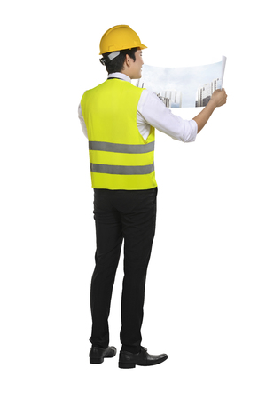 Young asian architect man looking at his blueprints isolated over white background Stockfoto