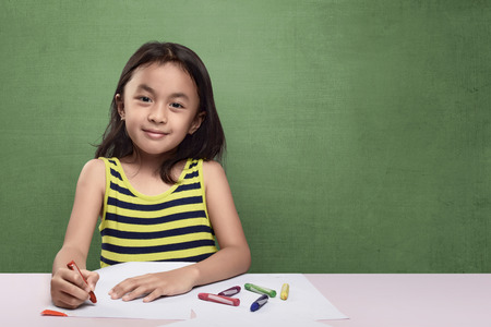asian art: Portrait of asian kid drawing with colorful crayon against chalkboard background Stock Photo