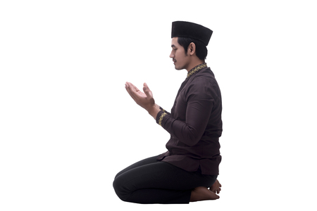 Handsome asian muslim man sitting and raising hand pray isolated over white background Stock Photo