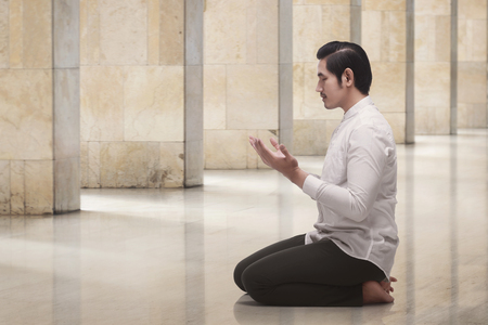 Handsome asian muslim man kneeling while praying in the mosque