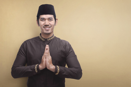Handsome asian muslim man wearing traditional dress praying against brown background