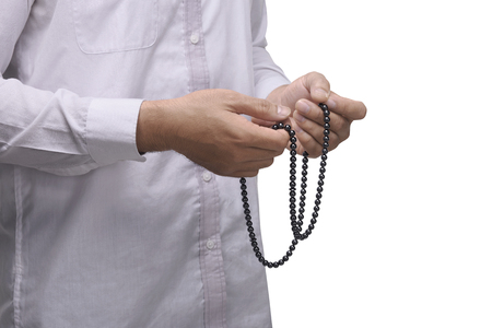 Hand of muslim man with prayer beads pray to god isolated over white background