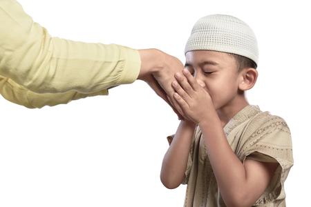 Kleines asiatisches moslemisches Kind in der weißen Kappe, welche die Elternhand lokalisiert über weißem Hintergrund küsst Standard-Bild - 77736656
