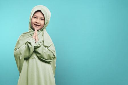 ヒジャーブ ドレスは、ブルーの背景の上に祈るとアジアのイスラム教の子供の笑顔