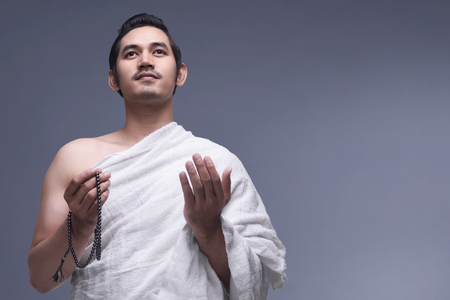 Young asian muslim man wearing ihram clothes with prayer beads against dark background Reklamní fotografie