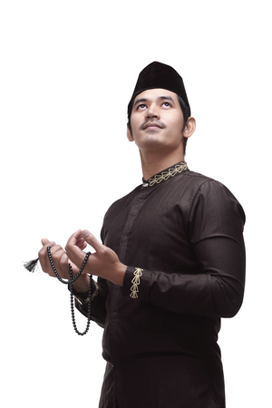 Religious asian muslim man in traditional dress praying isolated over white background