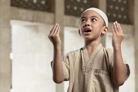 少年アジアのイスラム教徒はモスクの上げる手を祈ってください。