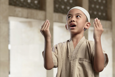 Little asian muslim boy is praying with raise hand in the mosque