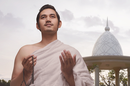 Smiling asian muslim man with ihram clothes holding prayer beads over sky background