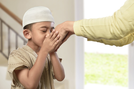 Little asian muslim boy with traditional dress kissing parents hand in the home