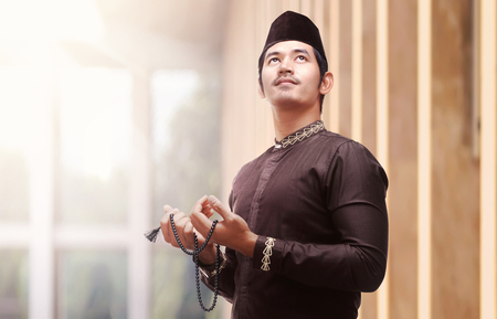Religious asian muslim man in traditional dress using prayer beads in the mosque