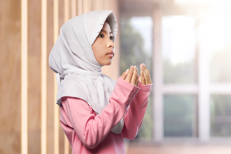 religious clothing: Portrait of asian muslim child raising hand and praying in the mosque Stock Photo