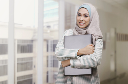 religious clothing: Beautiful asian muslim woman holding laptop in the office