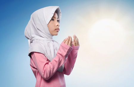 Little asian muslim girl praying to god over sunlight background Stock Photo