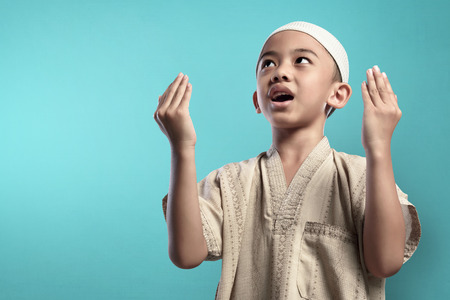 Little asian muslim kid raising hand and praying to god over blue background