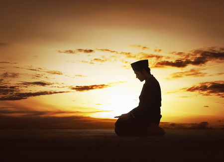 worshiped: Young asian muslim man worshiped praying to god over sunset background Stock Photo